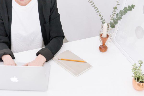 woman in blazer types on macbook