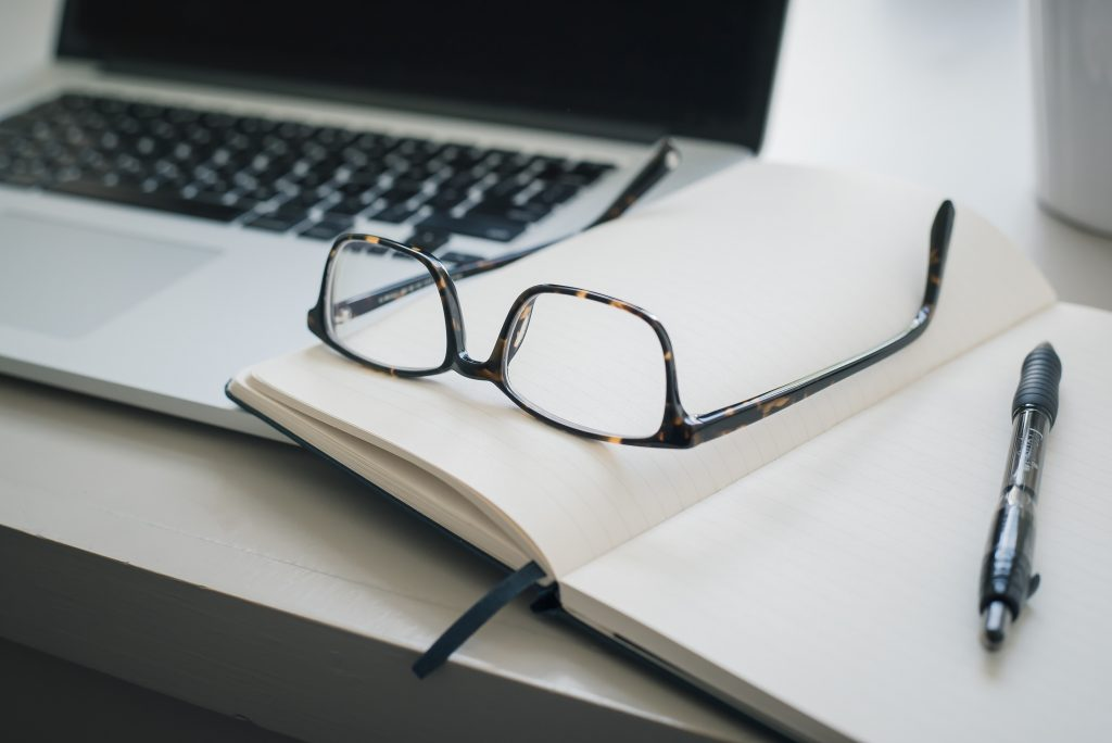 Photo by Trent Erwin on Unsplash, Glasses on a notebook with a pen, beside a mac